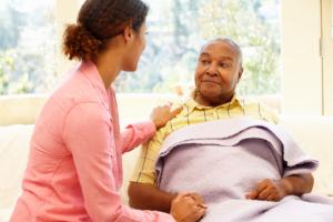 caregiver assisting elderly man in bed