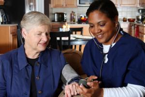 caregiver monitoring elderly woman's blood pressure
